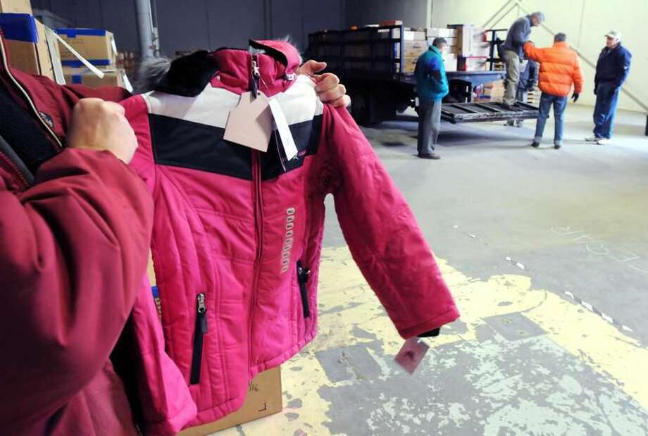 The Rotary Club of Orange bought 4200 warm, winter jackets to be given out to both Bridgeport and New Haven school children. Today they loaded up the coats for Bridgeport from a storage facility in West Haven. Club president Diane Eger of North Haven holds one of teh jackets. Photo by Mara Lavitt/New Haven Register1/5/12