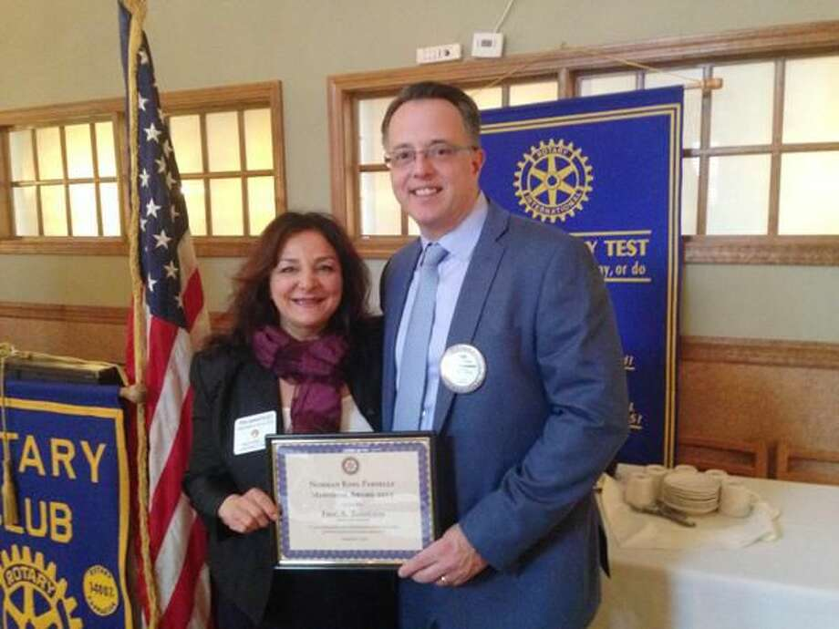 Submitted Photo Tina DeNapoles, president of Milford Rotary, left, presents the Norman K. Parsells Award to Eric Tashlein.