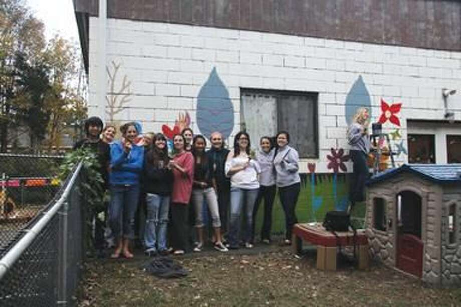 Submitted Photo by Mary Consoli National Art Honors Society members from Amity Regional High School pose in front of the mural they have begun to paint at Surreybrook Preschool Child Development Center.