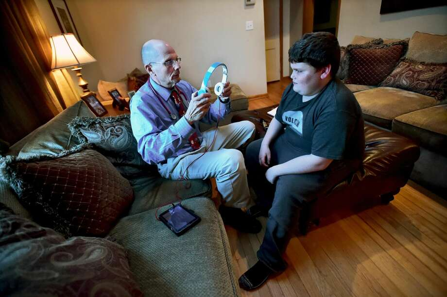 Catherine Avalone — New Haven Register Nurse practitioner Charles Wetmore explains how the hearing test will work to Joey Soto in the living room of the 12-year-old's Milford home. Wetmore, owner of Pediatric House Call Solutions, is on a follow-up house call after treating Joey for a recent ear infection.
