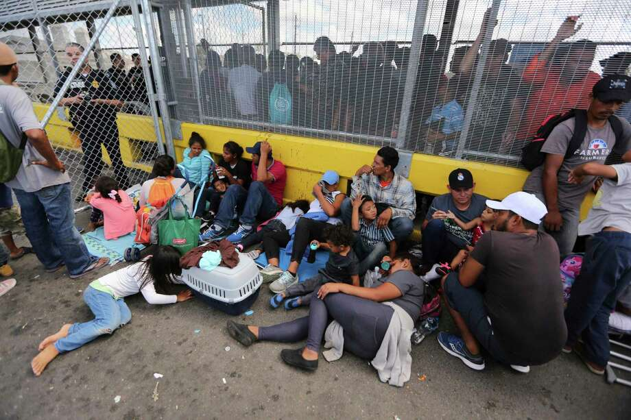 Migrantes se reúnen junto a una cerca fronteriza después de acampar en el Puente Internacional Gateway que conecta el centro de Matamoros, México, con Brownsville, Texas, el jueves 10 de octubre de 2019. Photo: Fernando Llano /Associated Press / Copyright 2019 The Associated Press. All rights reserved