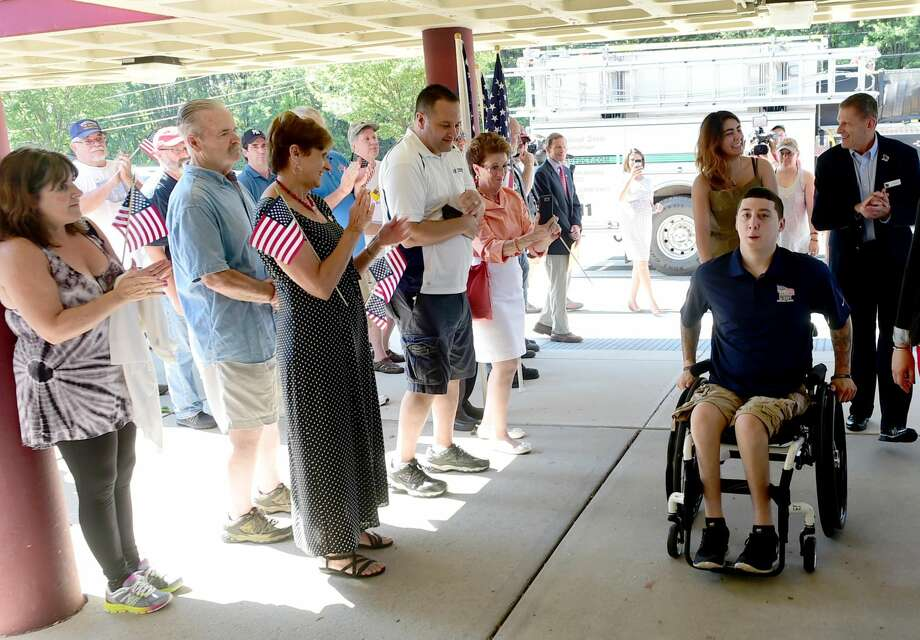 Peter Hvizdak New Haven Register Army veteran Sean Pesce, 24, wounded in 2012 in Afghanistan and paralyzed from the waist down, right, arrives Aug. 13 at Amity Regional Bethany Middle School.