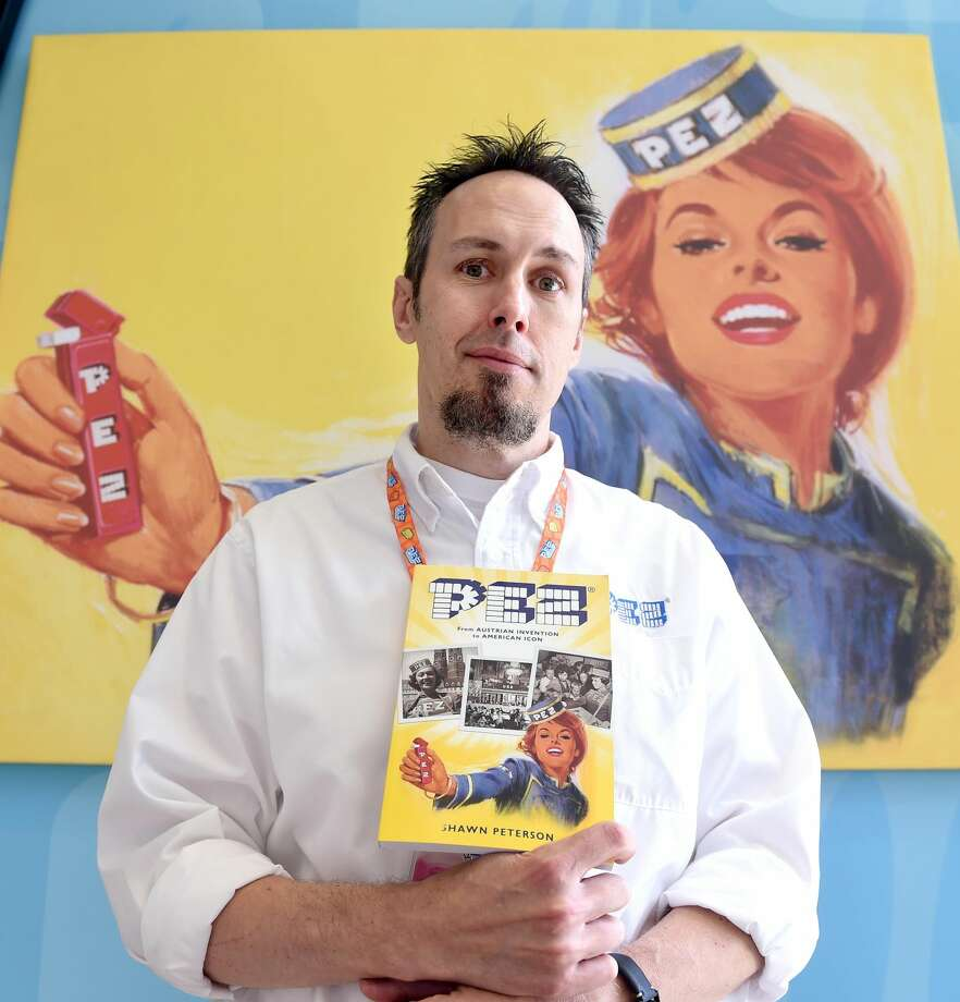 "Shawn Peterson, a manager at the Pez Visitor Center in Orange, is photographed with his book, ""Pez, From Austrian Invention to American Icon,"" on Aug. 15, 2016. Arnold Gold-New Haven Register"