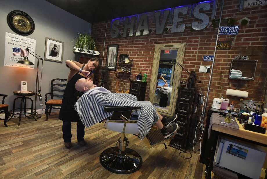 """Barber Susan Hushin, owner of BBS Shave Studio at 58 River Street in Milford, uses a straight razor to give Milford resident Bill Parry, a wet shave known as a """"Mr. Slick with a Gentleman's Shave,"""" Wednesday, August, 31, 2016. """"I would rather shave than cut hair,"""" said Hushin. (Catherine Avalone/New Haven Register)"""