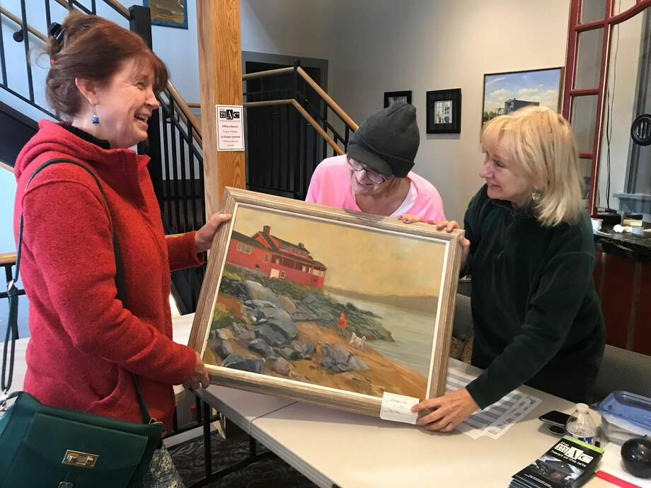 Artist Cathy Liontas, here with Arlene Morrell and Gayle Caro, submits an oil painting she entered into the judged exhibit.