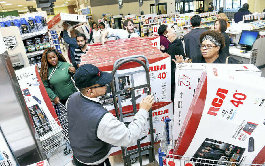 Yesmail Perez (center) helps customers with televisions on sale for the grand opening of ShopRite on Bull Hill Lane in Orange Sunday.