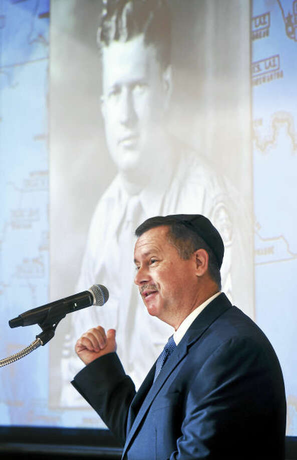 (Arnold Gold-New Haven Register) Pastor Chris Edmonds points to a photograph of his father, Master Sergeant Roddie Edmonds, during the 10th Annual Kristallnacht Commemoration at Congregation Or Shalom in Orange on 11/20/2016. Edmonds father risked his life and saved the lives of hundreds of Jewish-American soldiers at a Nazi POW camp by refusing to allow the soldiers to be identified and segregated by their religion.