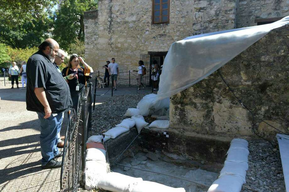 Ernesto Rodriguez, associate curator at The Alamo, looks into an archaeological dig area containing what appears to be the curved foundation of a watchtower at the northeast corner of the sacristy on Thursday, Oct. 10, 2019. The find gives the first physical evidence of a guard tower shown on two historic maps drawn by Edward Everett, one dating to 1846 and the second to 1848. Photo: Billy Calzada /Staff Photographer / San Antonio Express-News