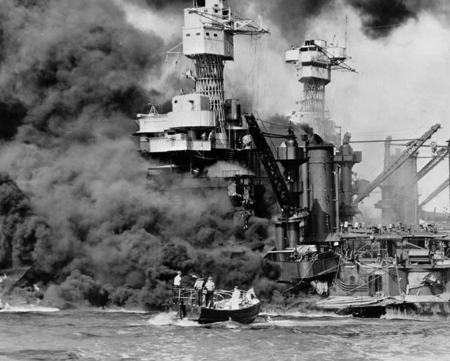 In this Dec. 7, 1941, photo, a small boat rescues a seaman from the USS West Virginia burning in the foreground in Pearl Harbor, Hawaii, after Japanese aircraft attacked the military installation.