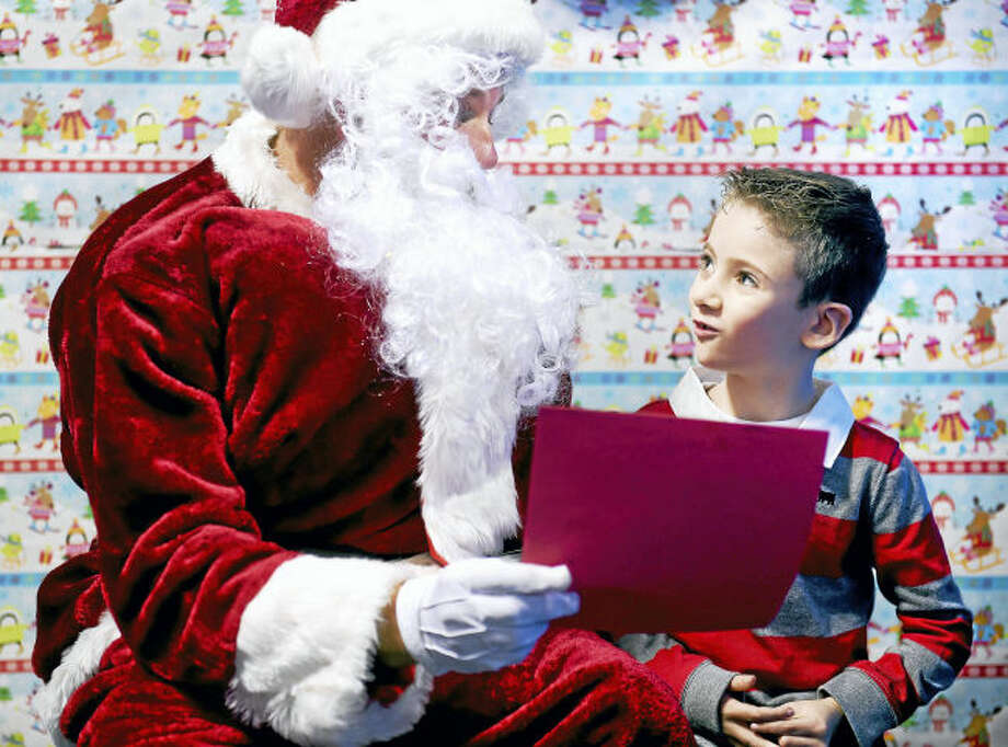 Santa Claus looks over the wish-list from Aiden Krynski, 6, of Monroe before giving him a gift at the ASD Fitness Center in Orange.