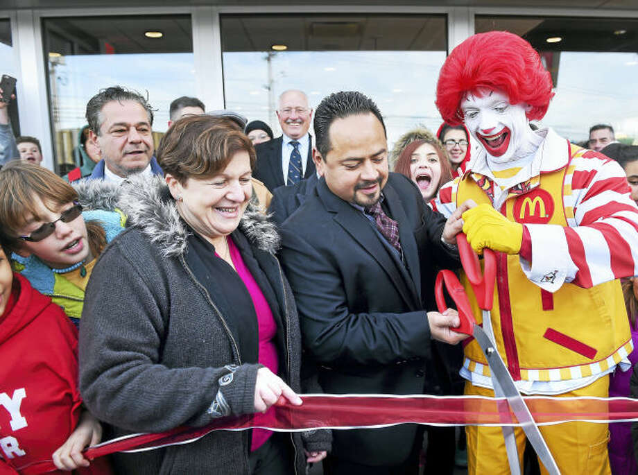 Left to right, Derby Mayor Anita Dugatto, McDonald's owner/operator Joe Rodriguez and Ronald McDonald cut a ribbon for the grand re-opening of McDonald's on Division Street in Derby on Dec. 19. In the background at left is Ansonia Mayor David Cassetti.