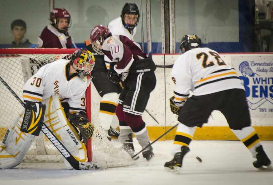(Melanie Stengel — Register) Milford's Brandon Argyros is caught betweeen Amity's Dalton Luciani and Keating Seymour in 2nd period action 1/8. Keeping an eye on the puck is Amity goalie,Brian Mosher.