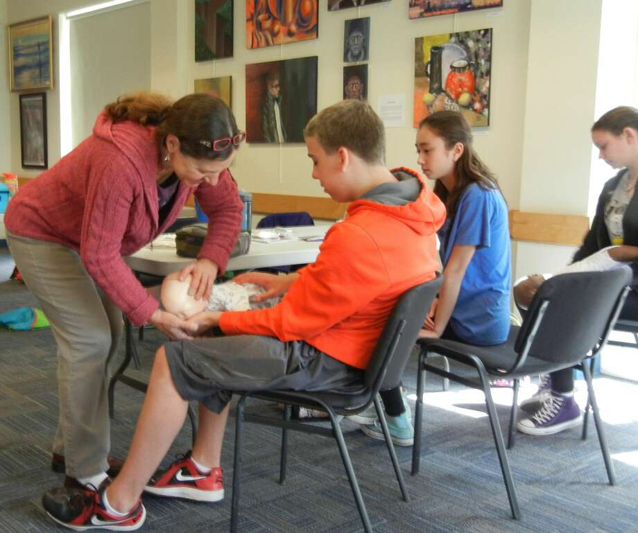 SUBMITTED PHOTO Red Cross instructor Anna Maria Mauhs shows students the proper hold for choking response at Youth Services' babysitter training.