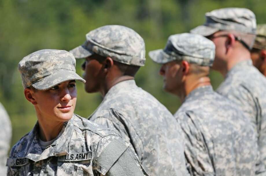 U.S. Army Capt. Kristen Griest, of Orange, Connecticut, left, smiles as she stands in formation during an Army Ranger School graduation ceremony, Friday, Aug. 21, 2015, at Fort Benning, Ga. Griest and First Lt. Shaye Haver became the first female soldiers to complete the Army's rigorous school, putting a spotlight on the debate over women in combat. (AP Photo/John Bazemore)