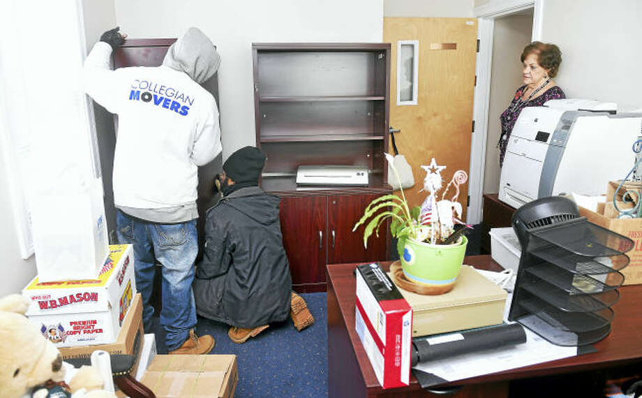 From left, Jerrod Preston and Kishon Phillip of Collegian Movers move furniture into the interim office of Maureen Piccolo, lead administrative assistant at Boys & Girls Village, on the Crown Corporate Park campus in Milford.