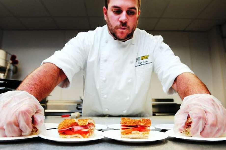 Dan Cole, assistant executive chef prepares an Italian BMT on garlic bread in the test kitchen at Subway World Headquarters in Milford on 8/28/2013. Garlic bread is being introduced at Subway restaurants on September 1.