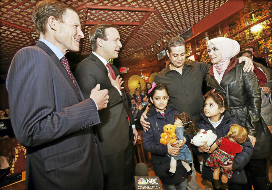 From left, U.S. Sen. Richard Blumenthal and Sen. Chris Murphy welcome Syrian refugees Fadi Kassar, his wife, Razan Ghandour, and their two daughters, Hanan Kassar, 8, and Layan Kassar, 5, at the Olive Tree Mediterranean Deli in Milford.