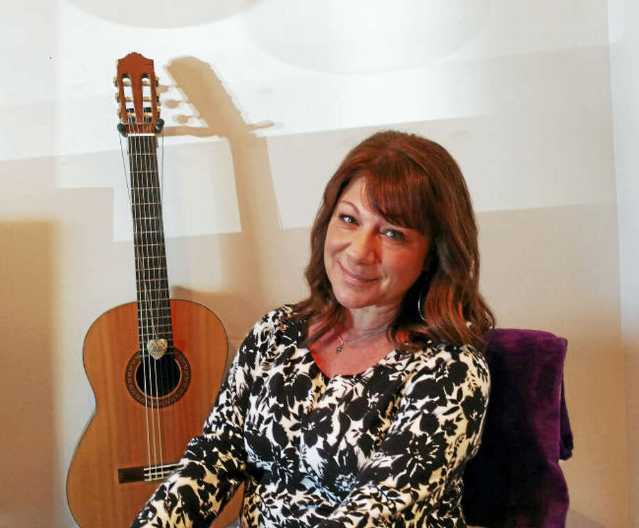 Donna Cimarelli sits in front of the guitar owned by her late daughter, Maren Sanchez.