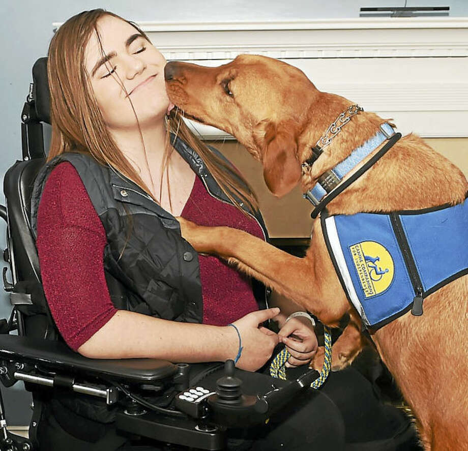 Dana Parrott, 14, of Milford, with Zinc, who was provided by Canine Companions for Independence.