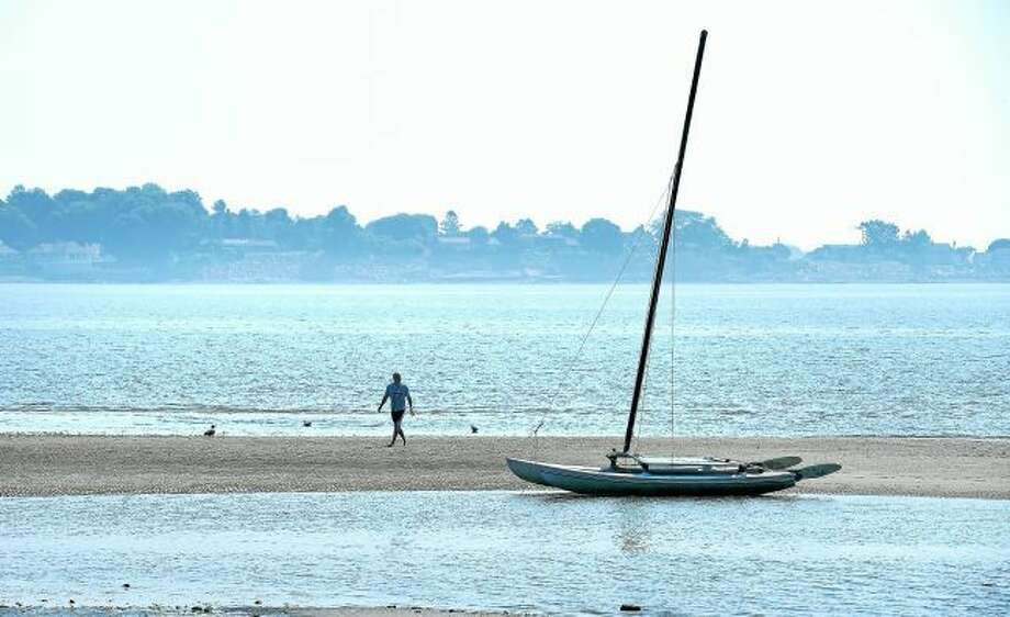 Milford Health Department Sanitarian Paul Scholz walks back to his car after getting a water sample in the waters off the tombolo at Silver Sands State Park in Milford in July 2015.