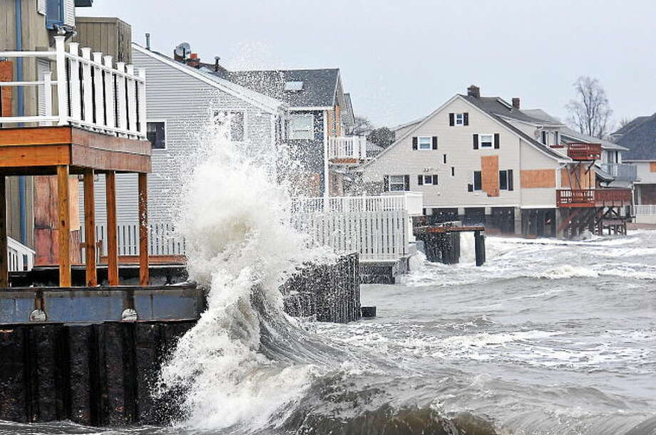 Waves slam against the homes along Cosey Beach in East Haven during low tide.