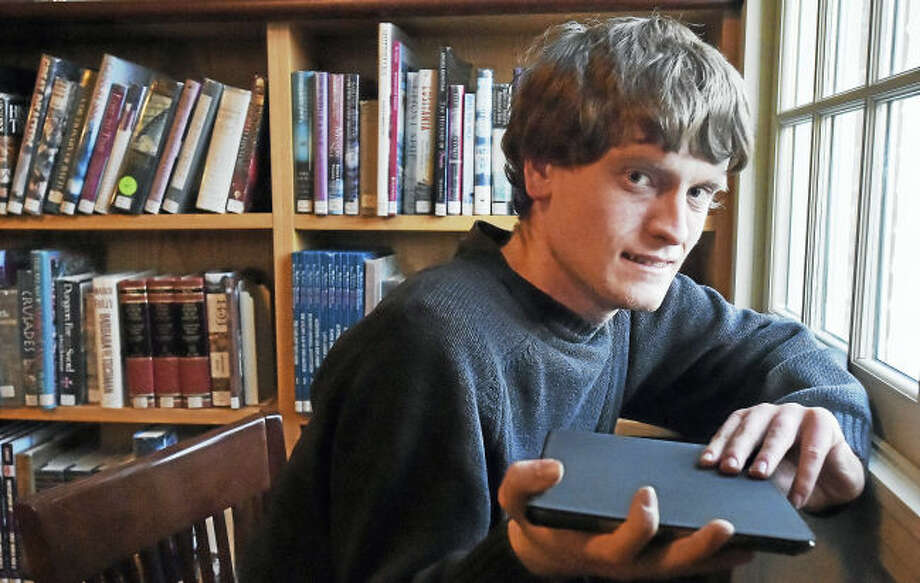 Madison resident Tommy Canning,22, holds his IPad, Wednesday, March 22, 2017, at the Atwater Library at 1720 Foxon Road in North Branford. Canning, who hopes to have a series of books he has written about animals and the environment published, will be holding workshops across the state at different libraries to get feedback on his work.
