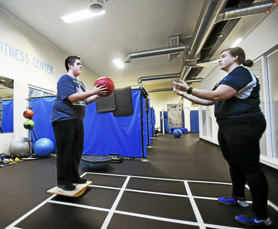 Standing on a balance board, Nick Keating, 16, passes a medicine ball to head trainer, Jackie Sanca, during a 30-minute personal training session at the ASD Fitness Center, 307 Racebrook Road, Orange.