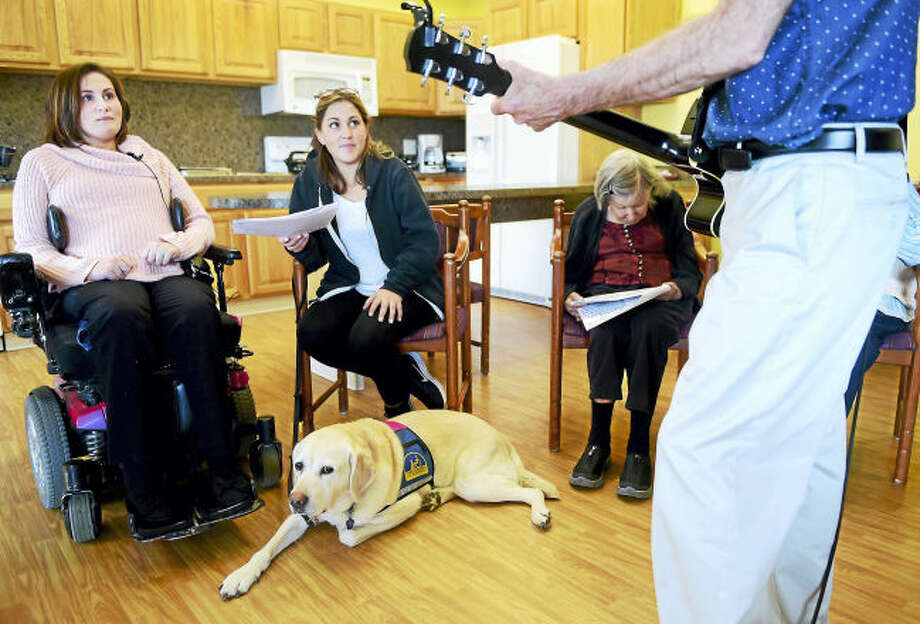 Alex Bode, 26, of North Branford, left, an intern at the Whitney Center memory support group in Hamden, observes a sing-along with Whitney Center clients earlier this month. Second from left is Bode's personal companion assistant, Lauren Stalzer, and her service dog, Rochelle.