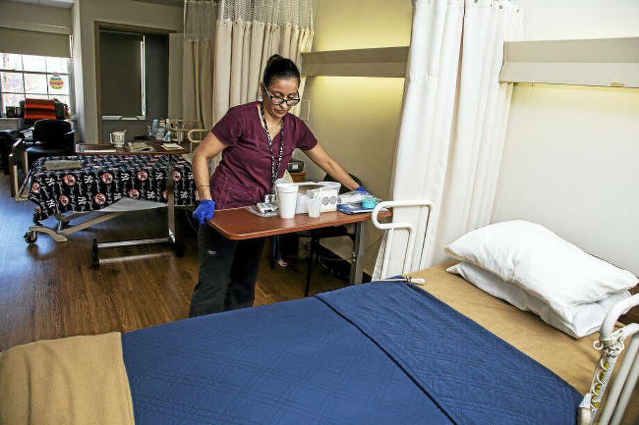 60 West nurse Irene Rivera, LPN, cleans a patient's room at the Rocky Hill nursing home.