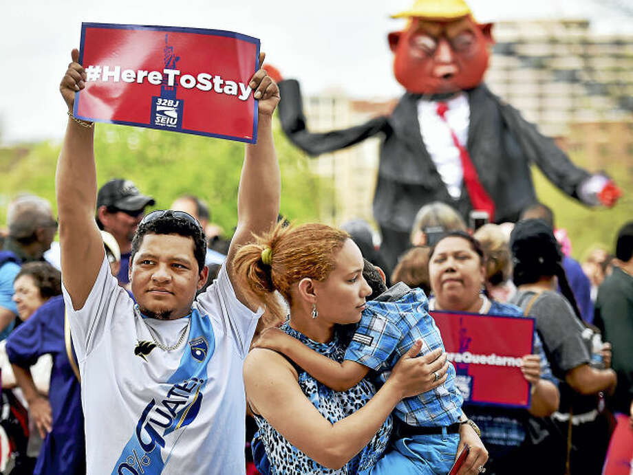"""Norwalk residents Alexander Cruz, 28, emigrated from Guatemala and his wife, Yeidy Cruz, came to the United States from the Dominican Republic who is holding their 4-year old son Dylan who has his eye on the giant-sized Donald Trump puppet at the """"Here to Stay"""" immigrant rights rally, Saturday, where hundreds of residents from across Connecticut gather at the State Capitol in Hartford."""