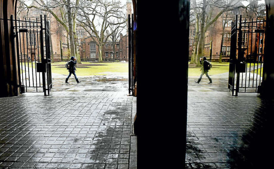 A passerby on the Yale University's Old Campus is mirrored in a reflection on a display case inside Phelps Gate.