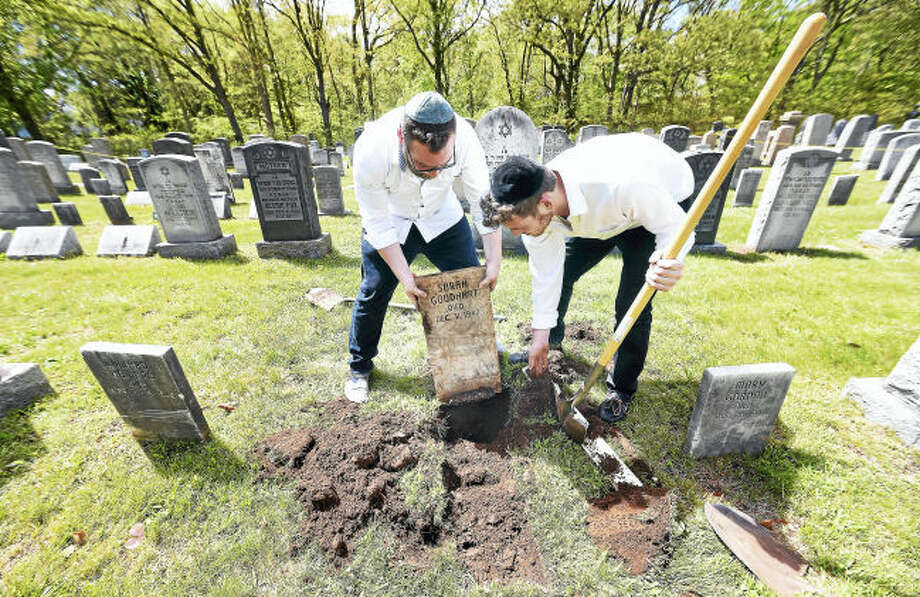 Eli Shuchatowitz, left, and Ari Weinstock of Yeshiva Meor Dovid in New Haven unearth a tombstone at the Hebrew Free Cemetery in East Haven during a recent event to repair, clean and map the cemetery.