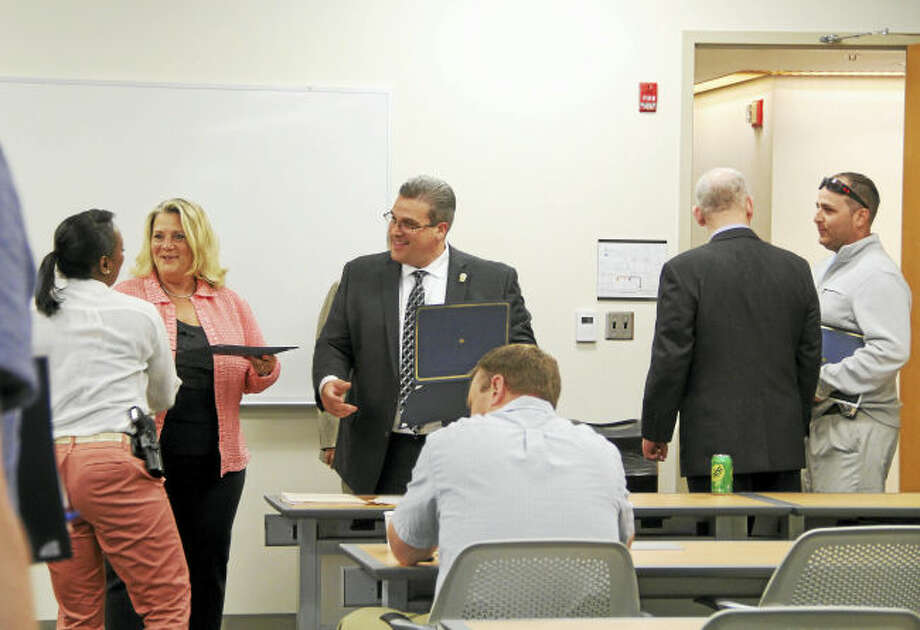 Lt. Herbert Johnson and Lisa Dadio, a lecturer at the University of New Haven, pass out certificates to attendees of the first regional detective school Friday.