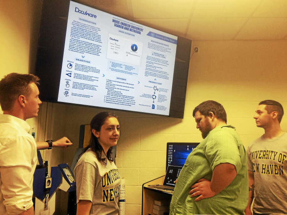 University of New Haven computer science students Samuel Perreault of Providence, R.I., Arianna Conti of Brewster, N.Y., Donald Sbabo of North Haven and Joseph Ricci of North Haven talk about the new voice recognition filing software program they created for DocuWare, a Wallingford-based document management company, as part of a senior project for Assistant Professor Frank Breitinger's Senior Design class.