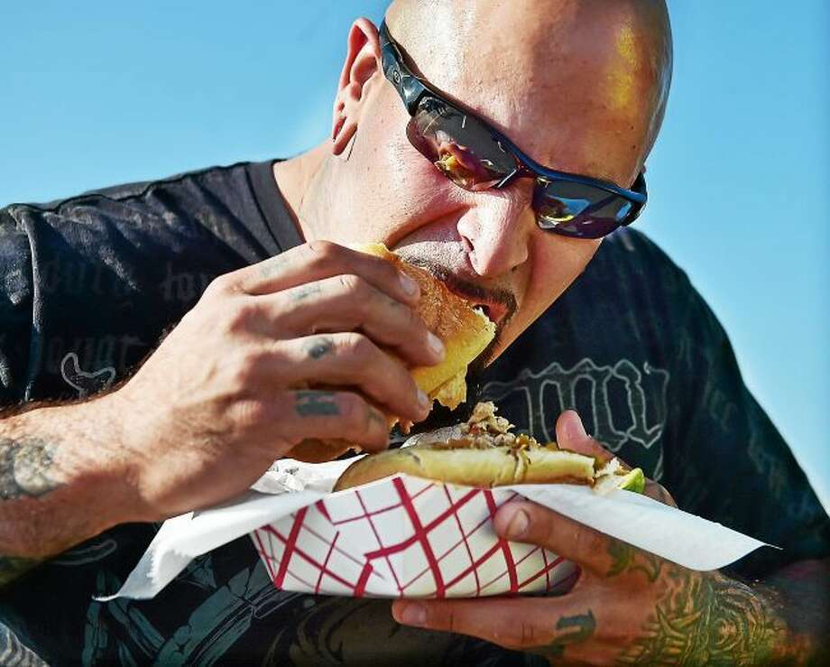 A festival-goer takes a bite out of a grinder at a New Haven festival in 2015. Orange will have its food truck fest today.