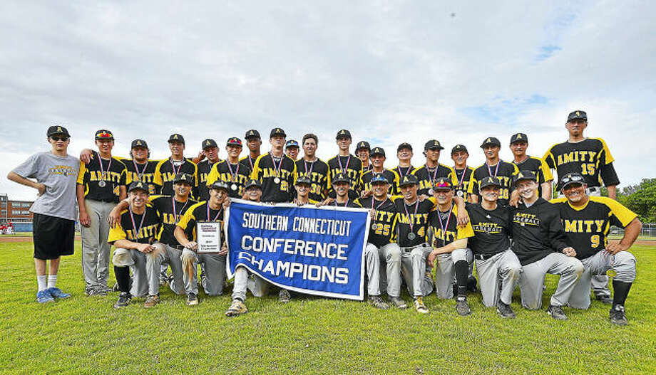 Members of the Amity baseball team pose with the championship banner after beating Fairfield Prep 11-5 for its third straight SCC championship Saturday at Piurek Field in West Haven.