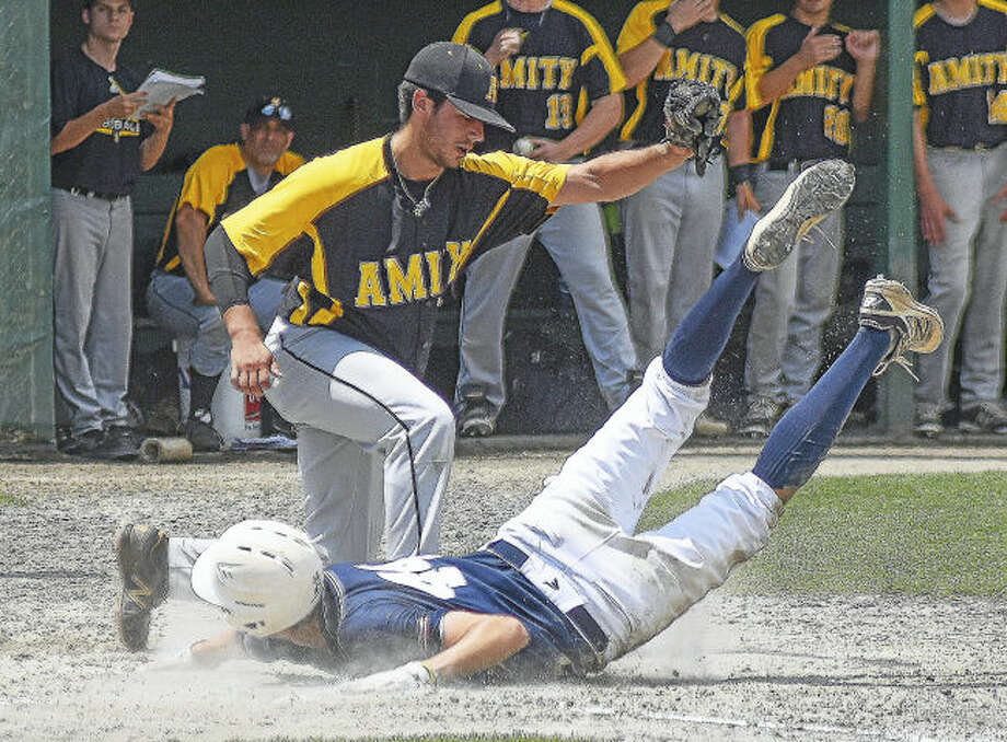 Amity pitcher Max Scheps, top, tags out Staples' Michael Fanning at the plate after a wild pitch during Saturday's Class LL championship game at Palmer Field in Middletown.