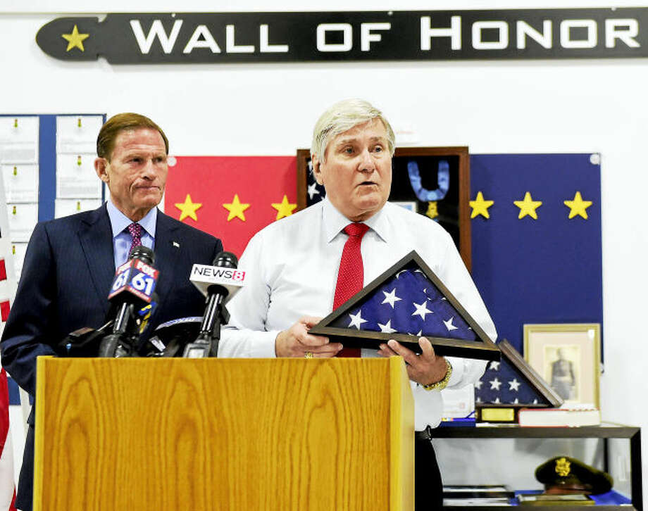 Terrance Gilbert Jr. of West Haven, right, the nephew of James W. Gilbert, who was declared missing in action at the end of World War II, speaks after a flag presentation by U.S. Sen. Richard Blumenthal, D-Conn., left, at the West Haven Veterans Museum and Learning Center.