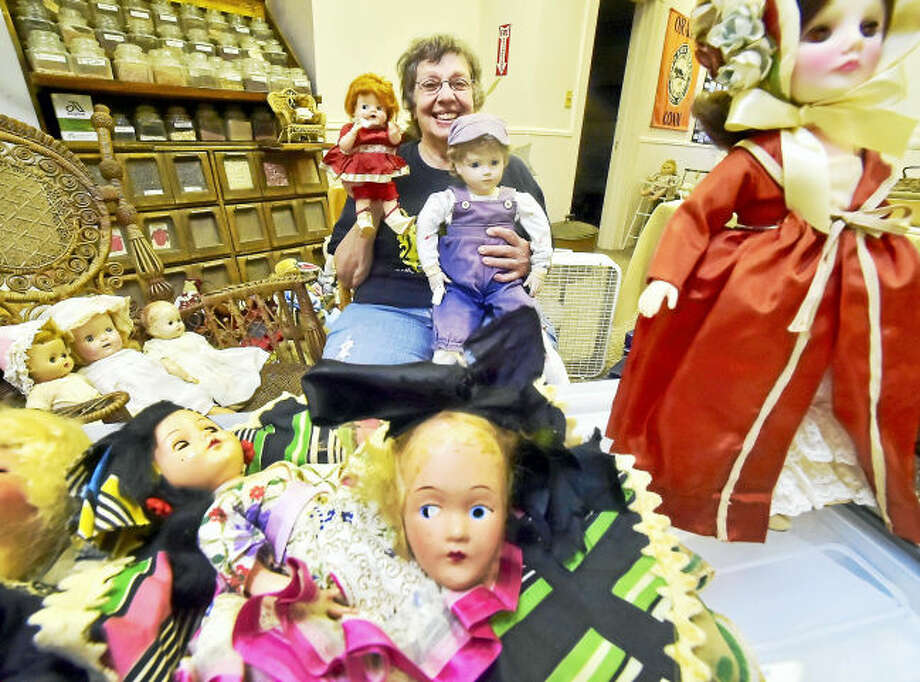 Ginny Reinhard, president of the Orange Historical Society, at the Academy Building in Orange with a handful of the many collectible dolls going up for sale as a benefit for the Bryan-Andrews House in Orange.