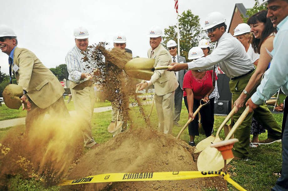Dirt flies at the ground-breaking ceremony for an addition to Boy's & Girl's Village's Charles F. Hayden Therapeutic Day School in Milford on Monday. Tossing the dirt is recent program graduate Chase Brown, 18, of West Haven.