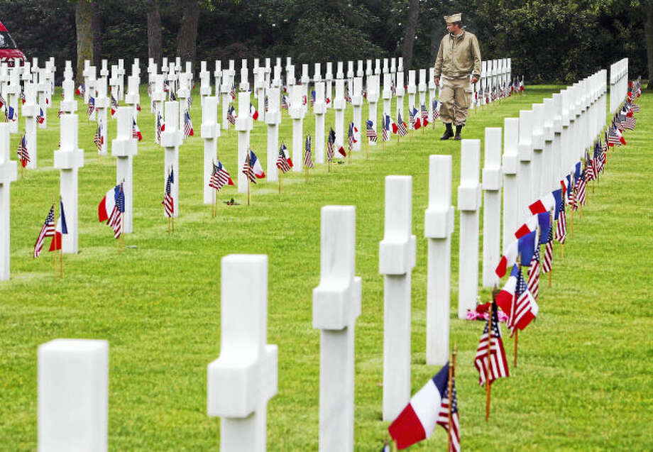 ** FILE ** An unidentified visitor wearing a U.S. military nurse uniform walks past graves at the American cemetary, in Colleville-sur-Mer, western France, in this June 6, 2007 file photo, marking the 63rd anniversary of the D-Day landings in Normandy. The Normandy American Memorial in Colleville-sur-Mer, best known for its sober rows of white grave markers of fallen U.S. troops in World War II, has at last gotten a visitor's center. (AP Photo/Remy de la Mauviniere)In this file photo, an unidentified visitor wearing a U.S. military nurse uniform walks past graves at the American cemetery, in Colleville-sur-Mer, western France, in 2007.