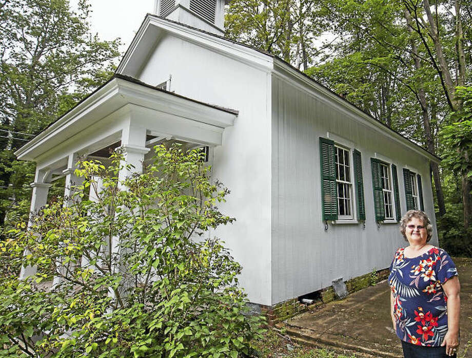 """Photo Derek Torrellas Melinda Elliott stands alongside the restored South School in Woodbridge. Her book, """"Connecticut Schoolhouses Through Time,"""" features historical and current photographs one- and two-room schoolhouses throughout the state.Melinda Elliott stands alongside the restored South School in Woodbridge. Her book, """"Connecticut Schoolhouses Through Time,"""" shows historical and current photographs one- and two-room schoolhouses throughout the state."""