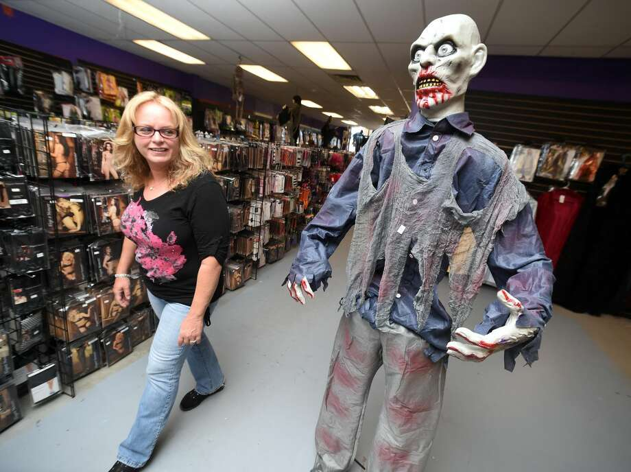 Patricia Kassas of Derby walks past a zombie in the Spooky Town Halloween Superstore in Orange on October 1, 2017. Arnold Gold / Hearst Connecticut Media