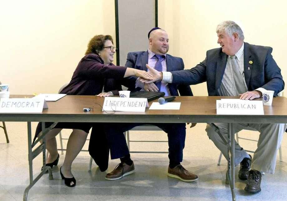 Democrat Margaret Novicki, left, Independent Alex DeAngelo, center, and Republican Orange First Selectman James Zeoli, all candidates for Orange First Selectman, shake hands after a debate Sunday morning at Congregation Or Shalom in Orange.