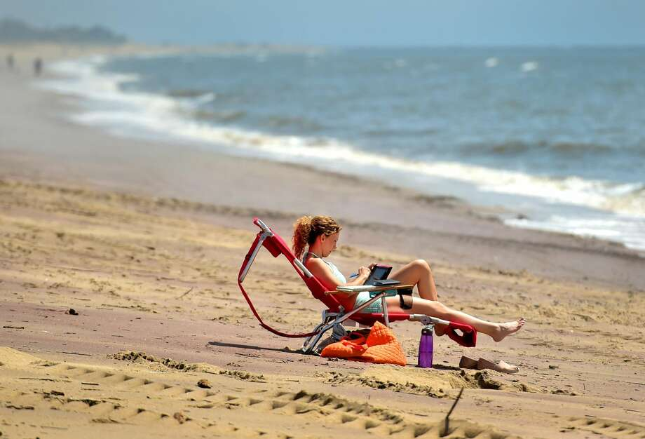 (Peter Hvizdak - New Haven Register) A woman, who wished to remain unidentified by name only enjoys her quiet time on West Beach at Hammonasset State Park Tuesday afternoon, May 2, 2017.