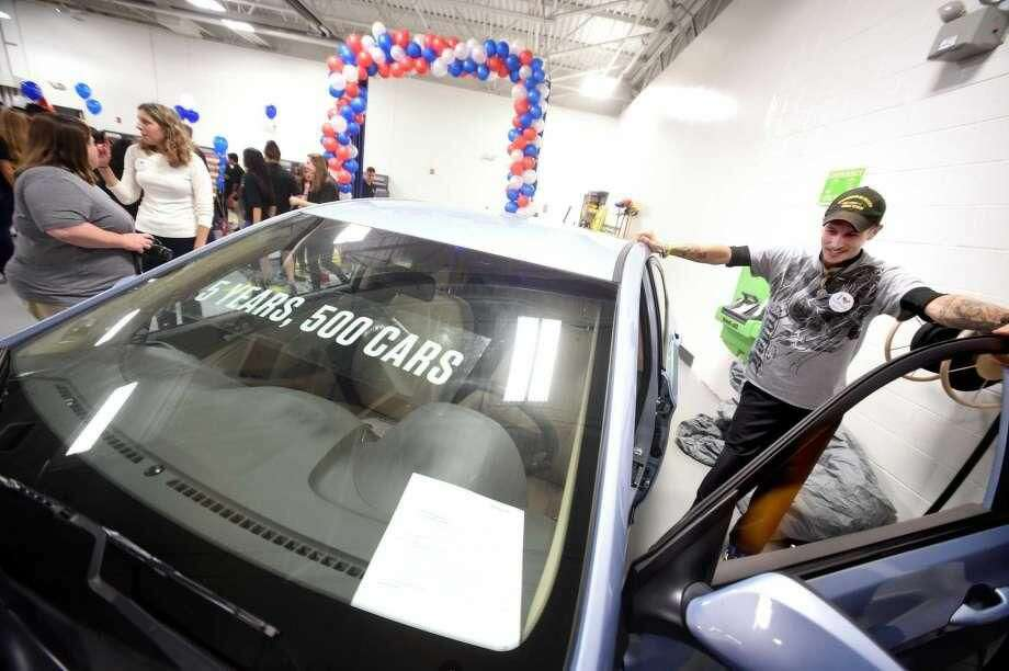 U.S. Army veteran Jacob Handy of Bristol looks over a 2014 Hyundai Accent he received at the Progressive Service Center in Milford during the company's fifth annual Keys to Progress event Thursday. The car was restored by Breezy Point Auto Body of Stratford.