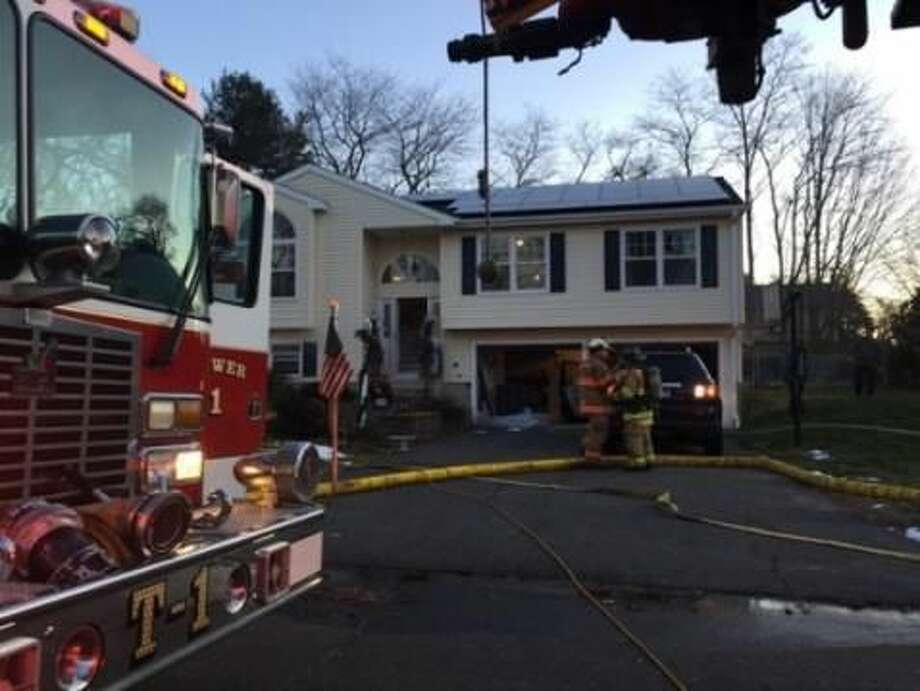 Firefighters inspect a home where a dryer fire broke out Wednesday.