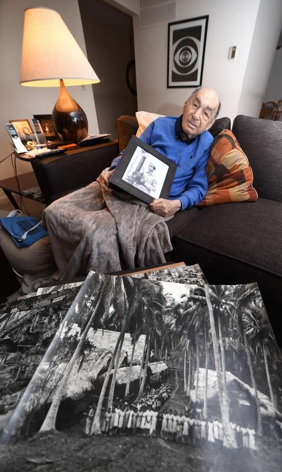 Ira Lewis holds a photograph of himself from his days as a photographer for the U.S. Army Signal Corps during World War II at his home in Branford. In the foreground is a photograph he took of a field hospital in the Philippines.