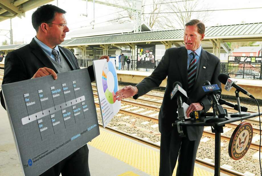 (Peter Hvizdak - New Haven Register) ¬ Milford Mayor Ben Blake, left, holds visual aids as U.S. Senator Richard Blumenthal (D-Conn) holds a press conference at the Milford Train Station Friday April, 18, 2014 about data on Metro-North Safetyfines ring back over a decade, what he intends to do to tighten safety standards for the railroad and how those standards will be used as a model for the country's railroads.