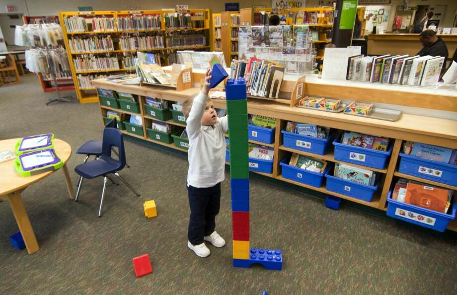 Brennan Lawless, 3, of Milford, builds a Lego tower while playing at the Milford Public Library.